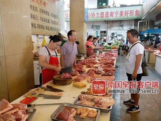 ▲8月31日上午,一市民在南宁麻村市场购买猪肉。
