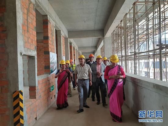 2019年5月24日,学校老师跟其他工作人员一起参观由中国协助重建的尼泊尔百年名校加德满都杜巴中学校园。新华社发(苏尼尔·夏尔马摄)