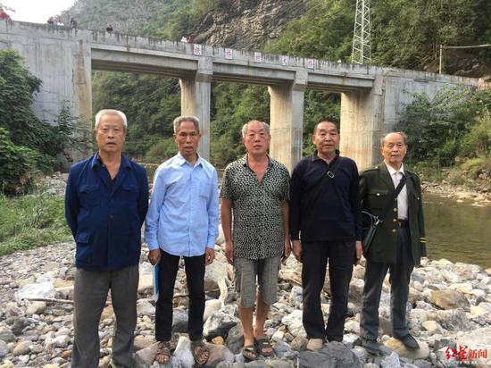 """右首:赵永贵、李先辉、安美蛟、甘宗良、杨发政,背后是他们主办修通的""""铁桥村大桥""""。"""