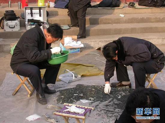 (2005年12月23日,乌国庆'左'在查找河南鄢陵县爆炸案的爆炸碎片。)