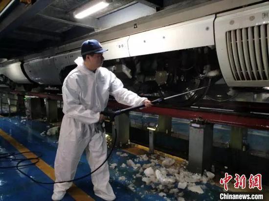 图为哈铁动车段工作人员清除动车组冰雪。 孙富阳 摄