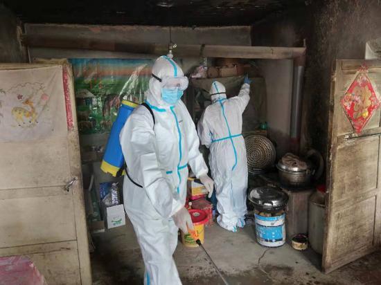 两名身穿防护服、戴着护镜、口罩的工作人员正在王思家的房屋消毒。 受访者供图