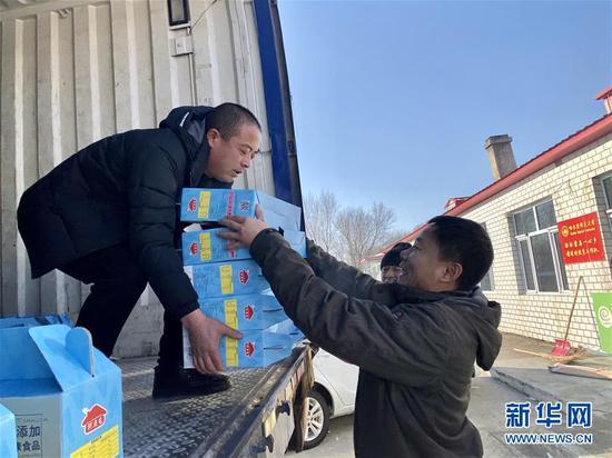 黑龙江省大庆市杜尔伯特蒙古族自治县一心乡前进村驻村工作队队长、第一书记慕海军(右)在搬送村里自产黏玉米(2020年1月4日摄)。新华社记者 杨思琪 摄