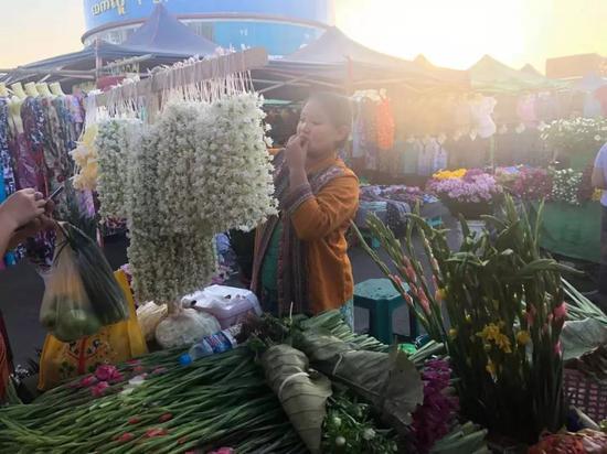 """▲习近平主席在署名文章中说:""""缅甸优美宁静的风光、绚丽多彩的文化、勤劳淳朴的人民给我留下了深刻印象。""""这是1月15日拍摄的内比都集市,民众在挑选鲜花。新华社记者孟娜摄"""