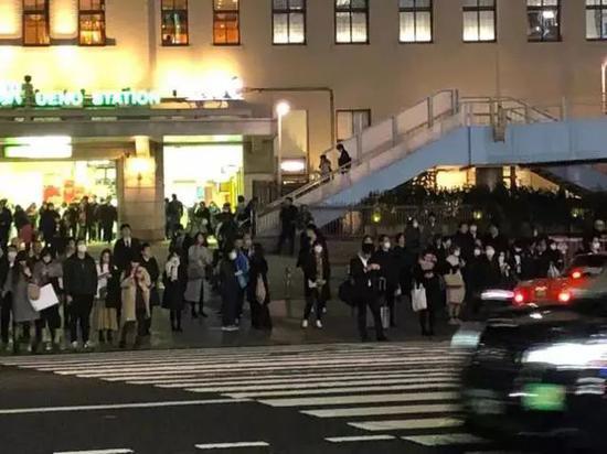图为1月28日,日本街上行人大多戴上口罩