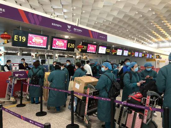 2月15日,西部航空包机护送河南省105名医护人员驰援武汉,一线空勤人员为医疗队开通绿色通道办理值机。