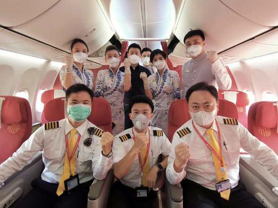 2月15日,海南航空第4架包机护送医疗队,机组人员为医疗队添油打气。