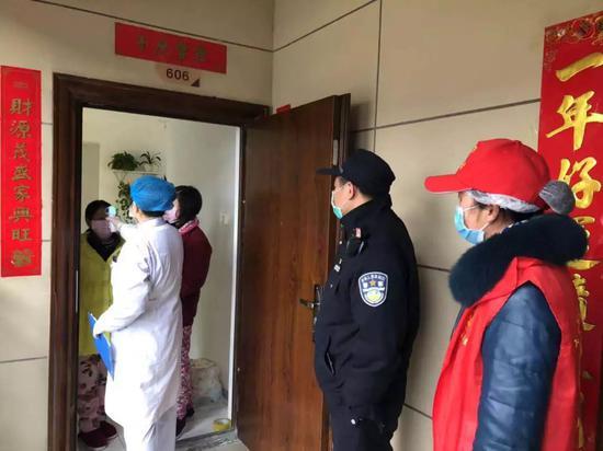 东西湖区长青街三民社区民警和社区人员一道上门进走体温测量 通讯员 余爽摄