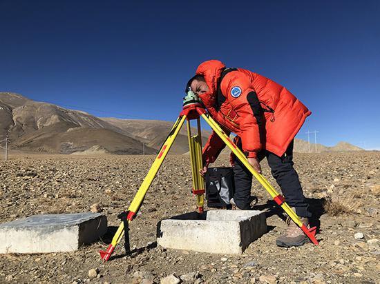 GNSS测量,测量队员正追求固定标准高度,准备安置链接卫星的设备 。