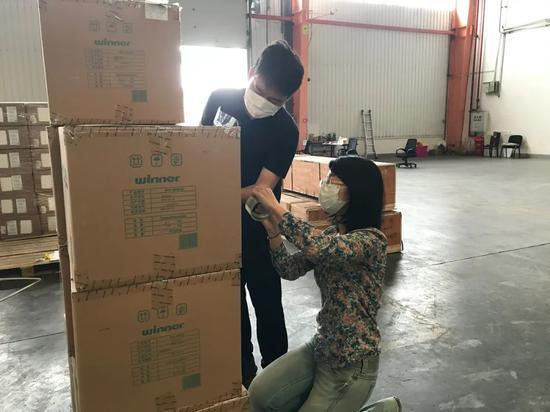 在汉欧班列货仓,魏琛(左)和同事整理即将发送到外国的援助物资,将写着祝福语的标签贴到纸箱上。