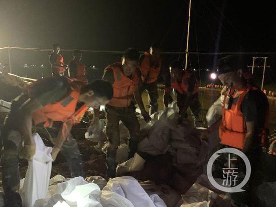 ▲7月15日晚,江西鄱阳县油墩街镇东联圩发生管涌,火箭军部队正在用沙袋进行围堵。受访者供图