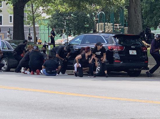 枪响后抗议者躲在汽车后面(图源:推特)