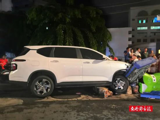 海南一轿车撞伤多人 一女子被卡车底路人齐力抬车