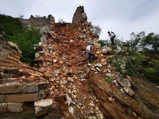 野长城自身存在各种险情,攀爬十分危险,图为工作人员在沿线辛苦地捡拾垃圾