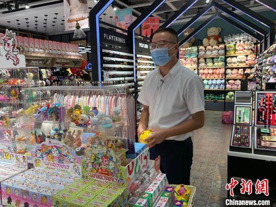 图为王志齐在商场给女儿挑选礼物 武一力 摄
