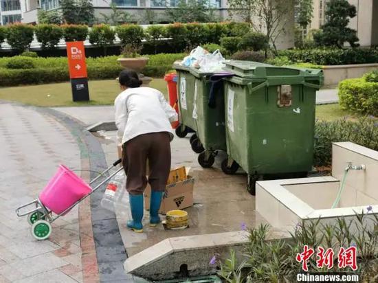 深圳一居民区附近,有人正在捡拾废弃的快递盒。受访者供图