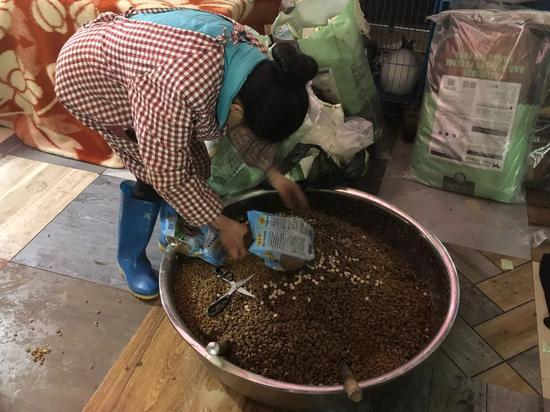 ▲工人把狗粮倒在直径近半米的大盆里,1300只狗一顿要吃七八盆。骚作者不祥狠狠干记者王翀鹏程 摄