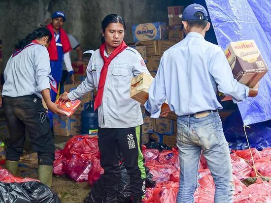 12月25日,在印度尼西亚万丹省板底兰县的灾民安放点,参与赈灾的做事人员为灾民搬运食物。(新华社记者杜宇摄)