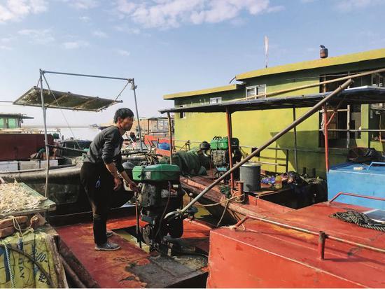 一名渔民拉起船头的柴油机,准备出湖。摄影/本刊记者 霍思伊