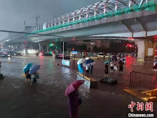 7月20日晚间,行人在路上趟水前行。 阚力 摄