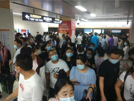 2021年7月20日,郑州,紫荆山地铁站内乘客在等待地铁。受强降雨影响,郑州地铁1、2号线调整运营区间。(图 人民视觉)