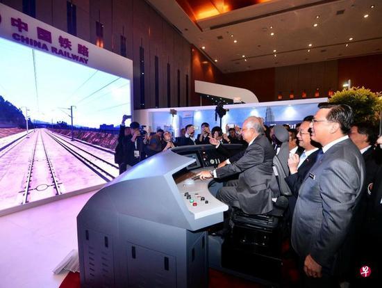 时仍马来西亚总理纳吉布(中)体验试驾中国高铁模拟器 图自联合早报