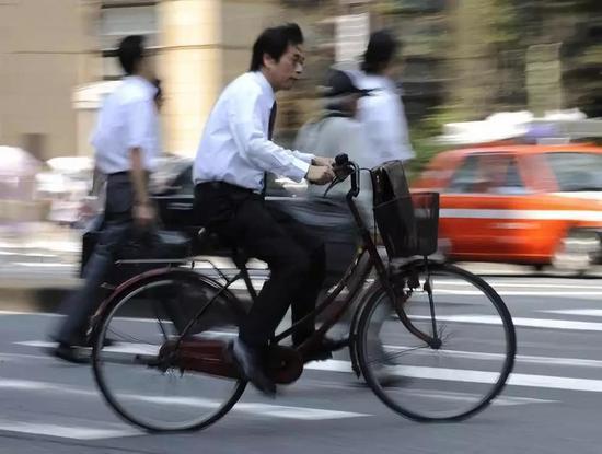 资料图片:日本东京骑车赶路的上班族(新华社/欧新)