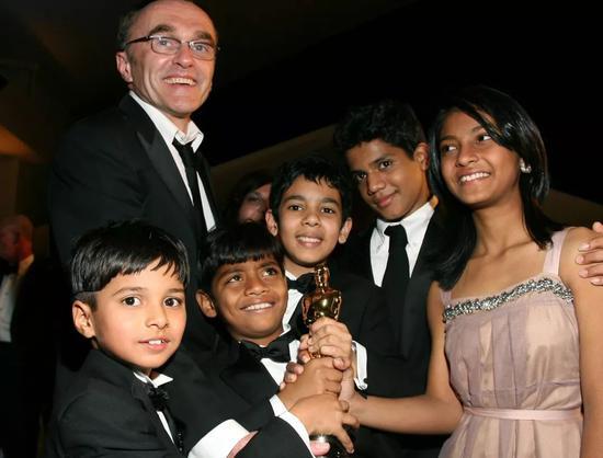 """印度电影《贫民窟的百万富翁》主要演员和导演获奖后手握""""小金人""""合影。新华社/法新"""