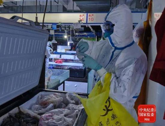 6月14日20时44分,中国疾控中心病毒病所溯源专家组成员在新发地农产品批发市场内采集冷冻海鲜样本。
