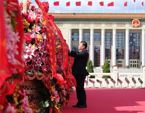 2018年9月30日上午,党和国家领导人习近平在北京天安门广场出席烈士纪念日向人民英雄敬献花篮仪式时整理花篮上的缎带。