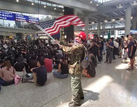 示威者在机场大厅挥舞美国国旗