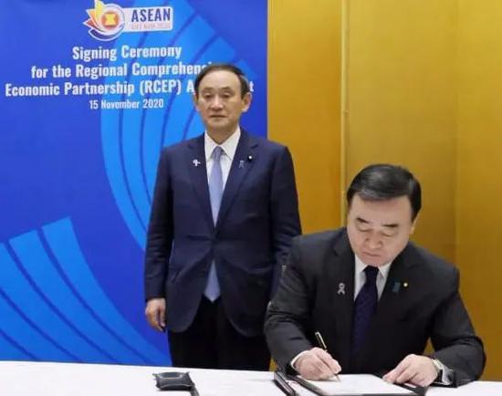 日本经济产业相梶山弘志(右)及首相菅义伟签定RCEP协定