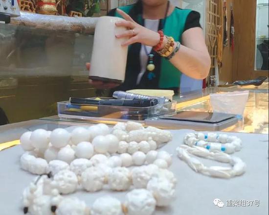 2018年8月11日,北京十里河雅园国际珠宝厅内,一猛犸象牙销售商向记者展示店内隐藏的现代象牙制品,其手中拿的是现代象牙所制的笔筒。 新京报记者王嘉宁 摄