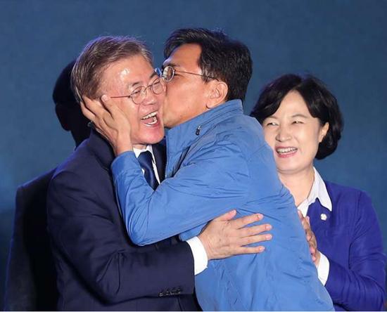 2017年5月9日,在首尔光化门广场进走的新任总统致辞时,时任忠清南道知事安熙正骤然亲了一下刚获胜当选总统的文在寅,外达甜美和祝贺。右一为时任共同民主党党首秋美喜欢。