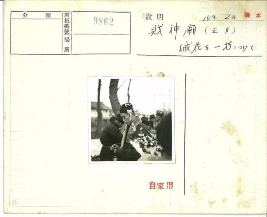△1939年2月,正月里,财神庙中的人头戴一簇花。