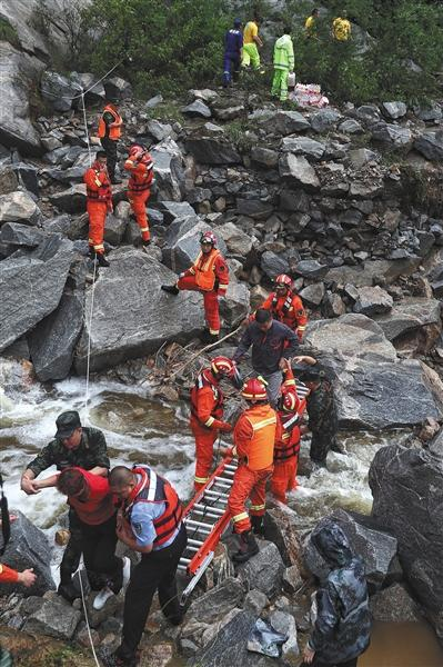 7月16日,密云琉辛路某段,抢救人员将被困游客转移出惊险地带。