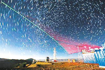 """图为""""墨子号""""量子科学实验卫星与阿里量子隐形传态实验平台建立天地链路(2016年12月9日摄,合成照片)。 新华社记者金立旺摄"""