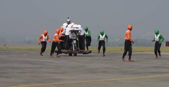 印度媒体视频直播,刚开始并不是所有58个人都在摩托车上,部分人在跑动中登上摩托车,并且要保持整个车辆的平衡。