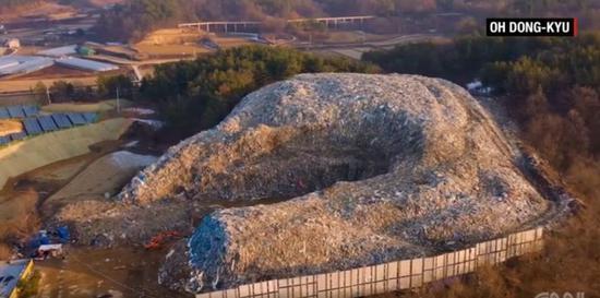 (图为义城郡的巨大垃圾山,注意与左下角的房屋作对比 图源:CNN)