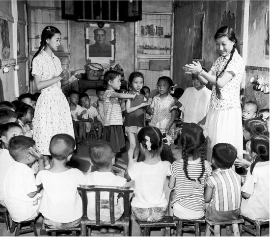 1958 年,国内一小儿园先生带孩子们做游玩(视觉中国供图)