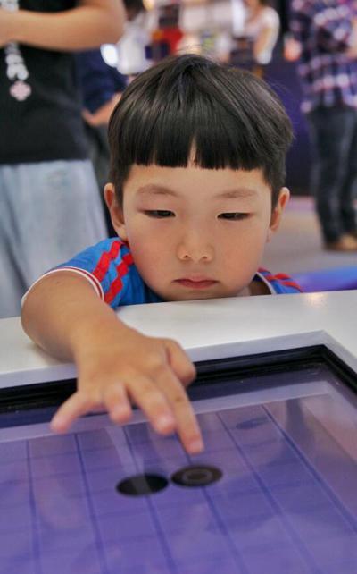 """""""互联网之光""""博览会上,小朋友正在与智能电脑对弈。石磊摄 光明图片/视觉中国"""