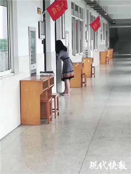 △担心打扰上课,她脱了高跟鞋赤脚在教室外行走 张春摄