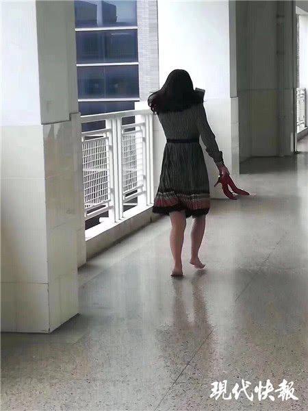 担心打扰上课 她脱高跟鞋赤脚在教室外行走