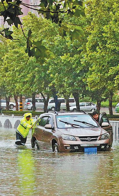 8月11日,山东枣庄,交警在积水中救助受困车辆。孙中喆摄(新华社发)