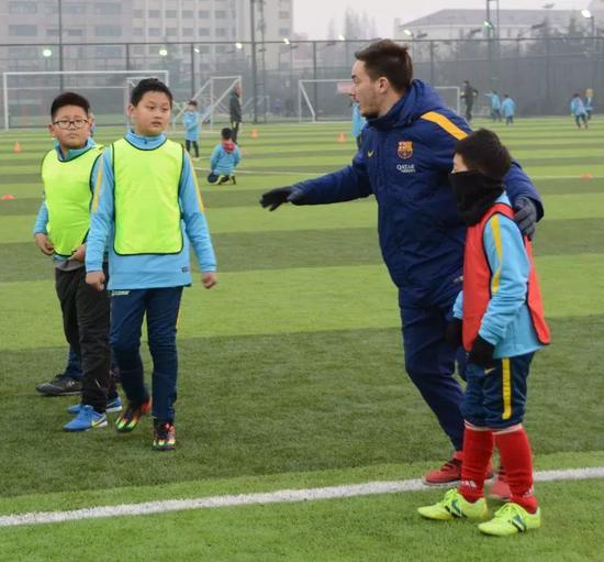 巴萨俱乐部青训教练阿尔贝·莫拉塔利亚(右二)在中国·巴萨青岛黄海足球学校为小球员讲解技术要领。新华社记者张旭东摄