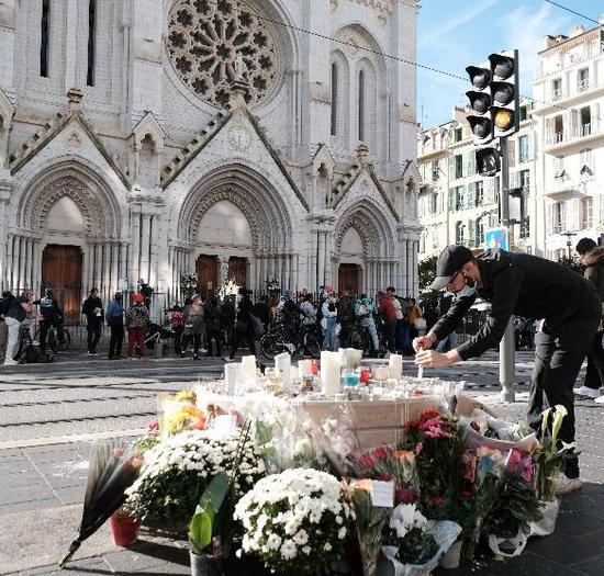 别名外子在法国尼斯圣母大教堂外点燃蜡烛悼念遇难者。 新华社 图