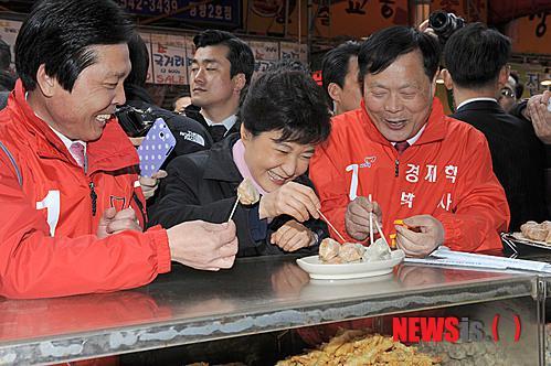 2012年3月,朴槿惠视察传统市场,品尝包子。(纽西斯通讯社)