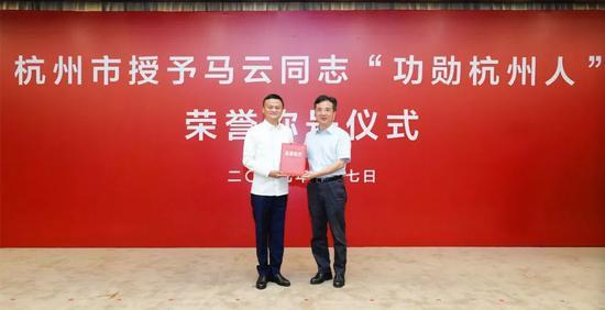 浙江省委常委、杭州市委书记周江勇(右)为马云授证书和印章