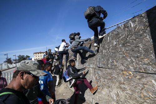 一些移民在墨西哥蒂华纳试图翻越障碍到达美墨边境(法新社)