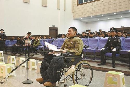 图为被告人张某坐着轮椅承受法庭审判。
